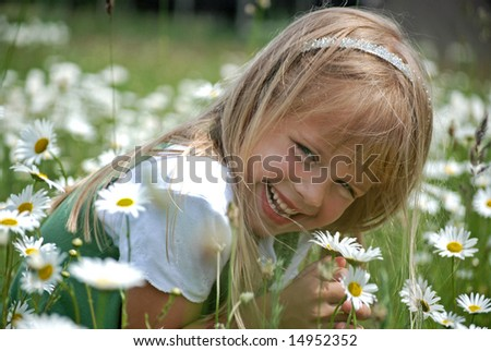 blond girl playing in daisy field - stock photo