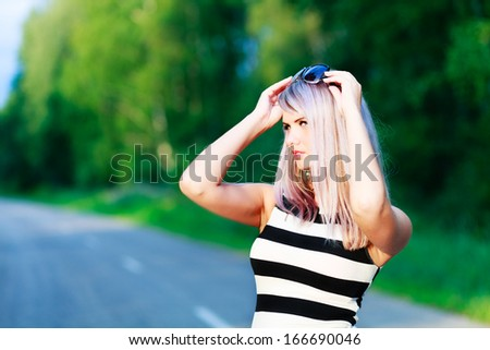 Blond girl`s in a stiped dress portrait on a road background. - stock photo