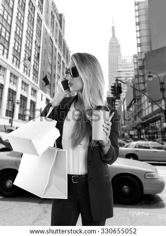 Blond girl shopaholic talking phone in fifth 5th avenue on New York Manhattan Photomount - stock photo