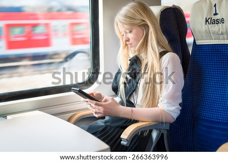 "Blond girl sitting in First Class of a train and holding a tablet in her hands. On the sit is written ""First Class"" in German. Selective focus. - stock photo"