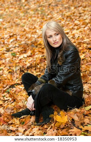 Blond girl sitting in yellow autumn leaves