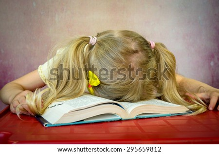 blond girl sleeping over open book - stock photo