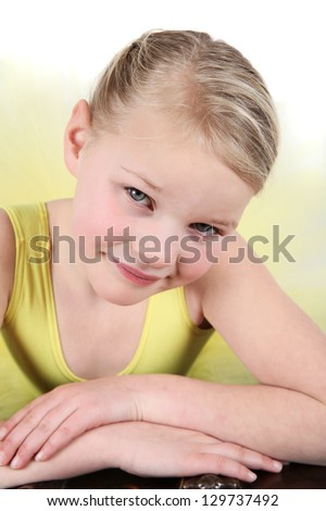 Blond girl wearing a yellow ballet tutu on white background