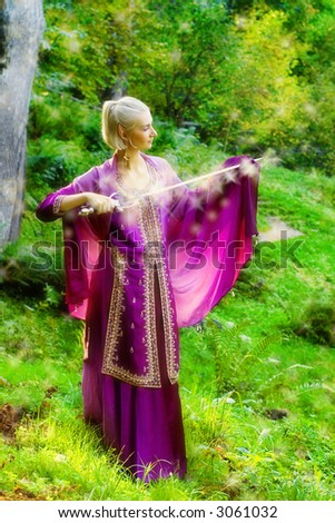 Blond girl with a magic sword - stock photo