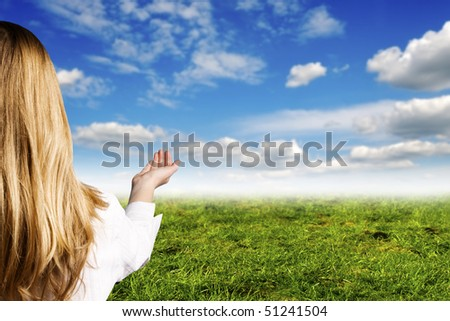 blond girl with an open hand, with blue sky and green meadow in background - stock photo
