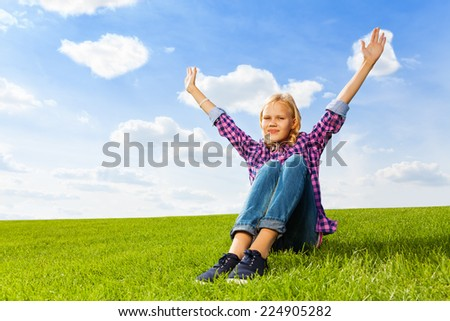 Blond girl with arms up sitting on green grass
