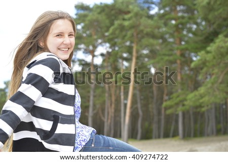 Blond girl with long hair is sitting and smiling. The pines are on the background. - stock photo