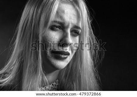 blond girl with pimply skin crying on black background, monochrome