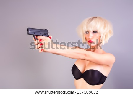 blond girl with the pistol - stock photo