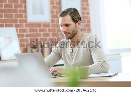 Blond guy sitting in front of laptop computer at home