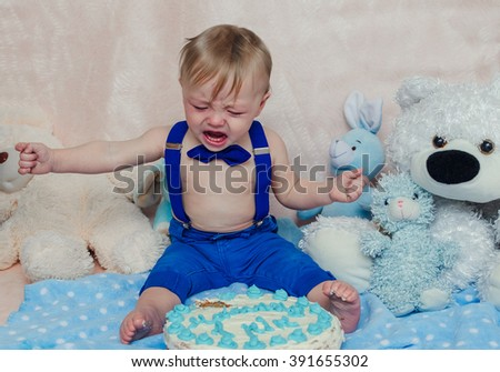 Blond hair blue eyed baby boy crying and screaming while eating his blue birthday party cake while sitting on cream background with foot in mess smearing icing - stock photo