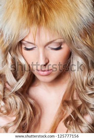 Blond hair woman in fur hat - stock photo