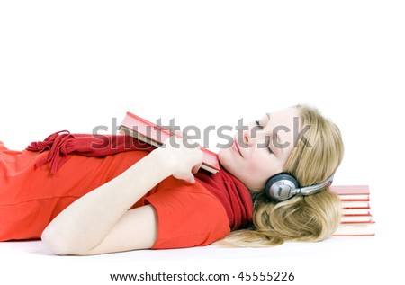 Blond hair young woman in headphones sleeping on heap of books - stock photo