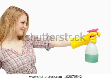 Blond-haired woman holding a spray bottle against white background - stock photo