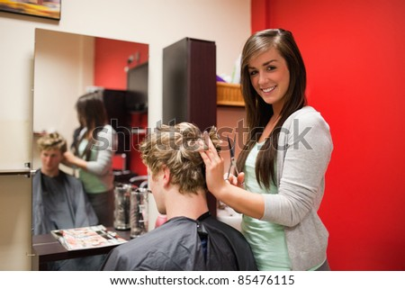 Blond-haired young man having a haircut with scissors - stock photo