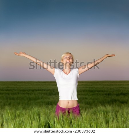 Blond happy woman in a wheat field at dusk