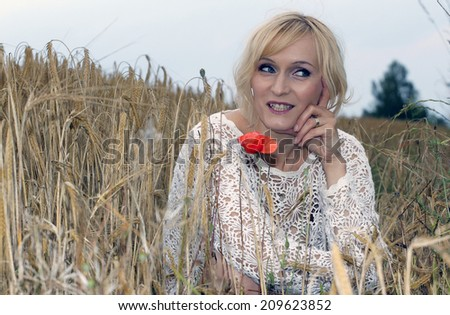 Blond happy woman lying in the wheat field. - stock photo