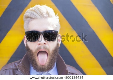 Blond hipster guy with beard sticking his tongue out.