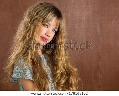 Blond kid girl curly hair portrait on retro vintage brown background - stock photo
