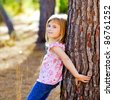 blond kid girl on autumn tree trunk in forest park - stock photo