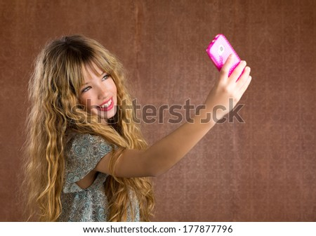 Blond kid girl taking pictures with mobile smartphone portrait on vintage background - stock photo