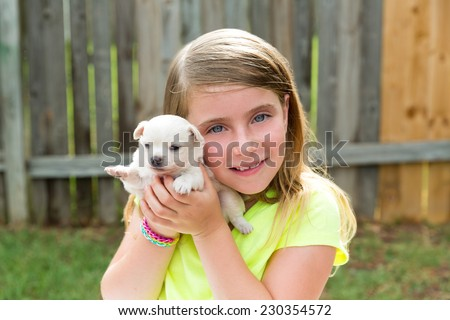 Blond kid girl with puppy pet chihuahua playing happy with doggy outdoor