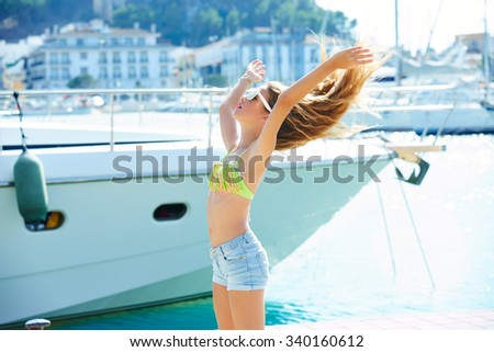 Blond kid teen girl in Mediterranean port of Spain shaking hair to wind