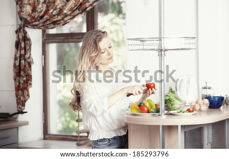 Blond lady at kitchen preparing vegetable for breakfast - stock photo