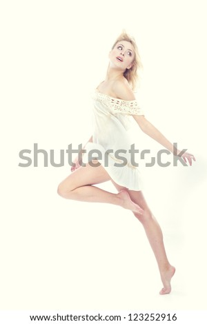 Blond lady dancing on a studio background - stock photo