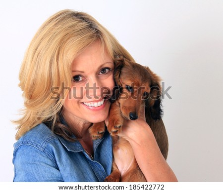 Blond lady holding a dachshund puppy.  - stock photo