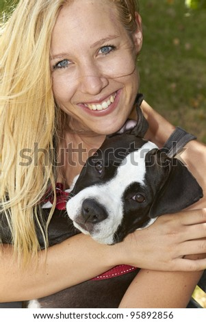 Blond lady holds her Pit Bull puppy - stock photo