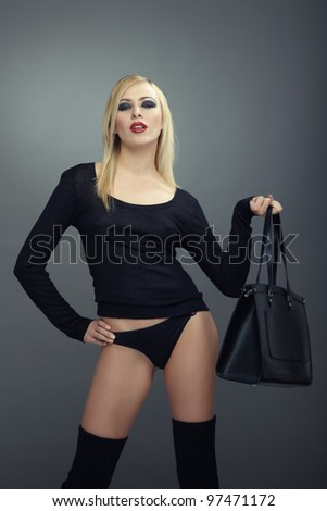 Blond lady in black lingerie with bag posing in the studio on a green background