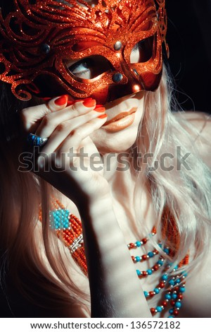 Blond lady in jewelry holding masquerade mask - stock photo