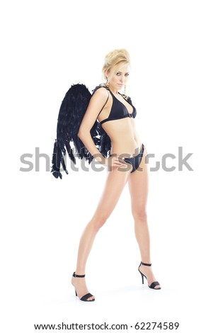 Blond lady standing akimbo in black lingerie with angel wings on a white background - stock photo