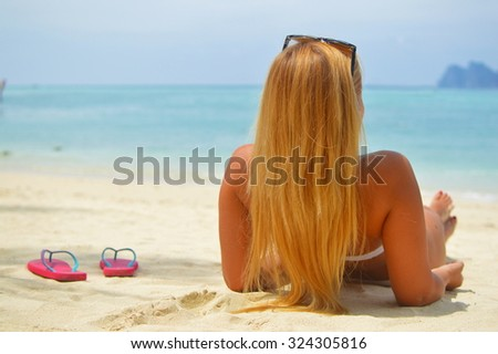 Blond laying on the beach watching the ocean - stock photo