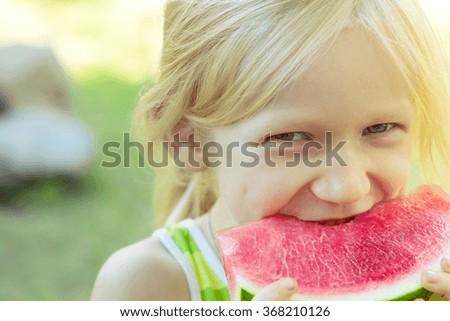 blond little girl eating watermelon - stock photo