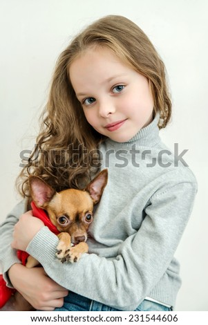 blond little girl holds small pet dog.