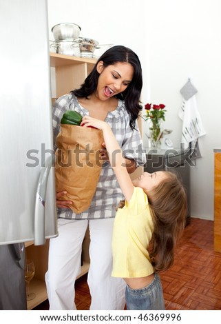 Blond little girl unpacking grocery bag with her mother in the kitchen - stock photo