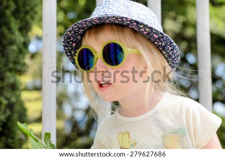 Blond little girl wearing trendy summer accessories as hat with floral pattern and mirrored sunglasses with yellow plastic frames while looking up outdoors, portrait - stock photo