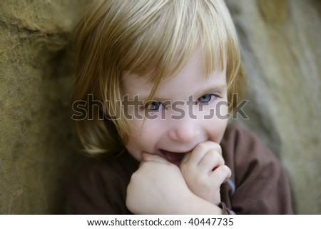 Blond little toddler girl with funny gesture portrait
