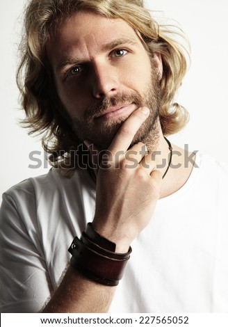 blond man touching his beard - stock photo