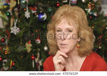 blond middle-aged woman in front of christmas tree in festive red sweater - stock photo
