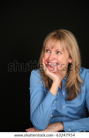 blond middle aged woman on black background smiling - stock photo