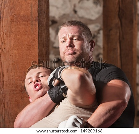 Blond mixed martial arts fighter being choked from behind - stock photo