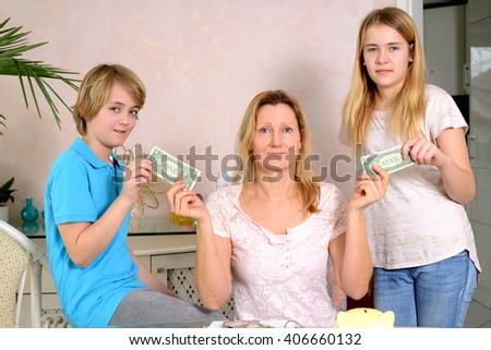 blond mother giving her children pocket money - stock photo