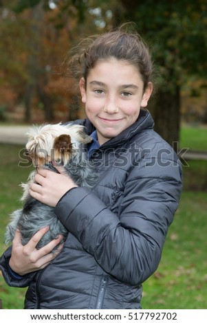 Blond preteen girl holding dog in the park