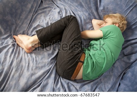 blond sad man lying on bed - stock photo