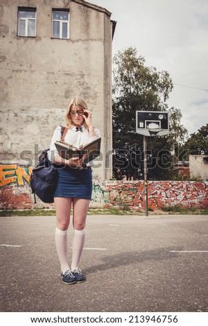 Blond school girl with nerd glasses in empty schoolyard. Selective focus. - stock photo