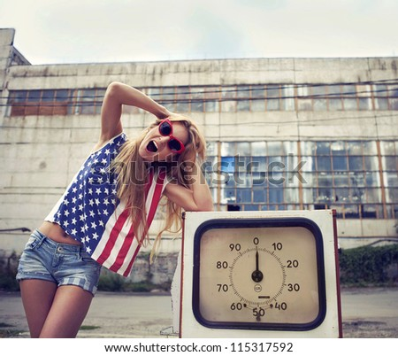 Blond screaming girl holds hands on her head standing on damaged gas station - stock photo