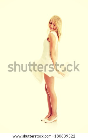 Blond sexy woman in white skirt blowed by wind - stock photo